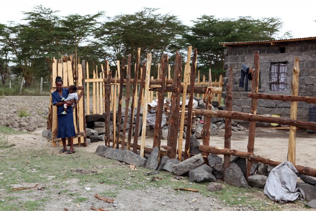Mary Njeri Machavia utenfor huset hun har bygd med lån fra Tuinuane. Nærmeste nabo er Lake Nakuru National Park.